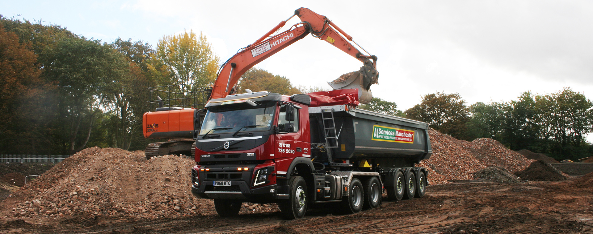 Articulated tipper being loaded at demolition site